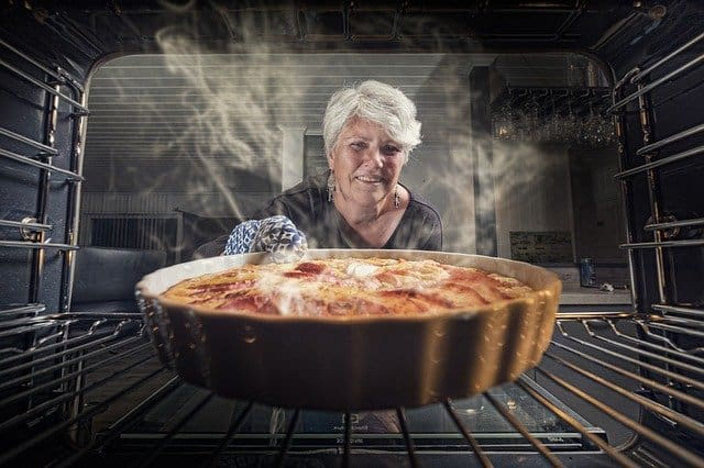 A pizza sitting on top of a metal pan on a stove top oven