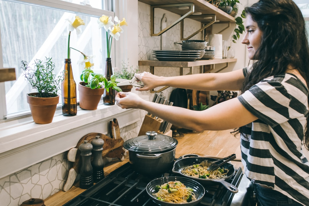 A woman cooking in a kitchen preparing food